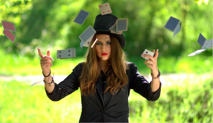 a woman playing cards and perform a magical shows thru using playing cards and floating it