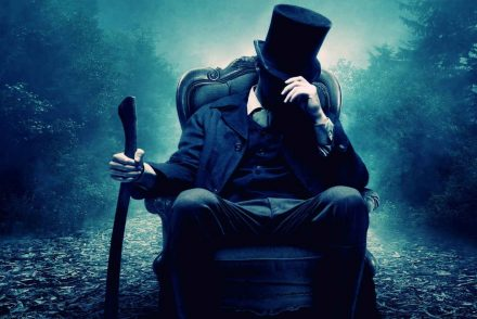 a magician sitting on a chair with his hat down