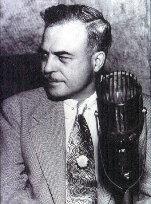 B&W photo of Milton Erickson in front of microphone