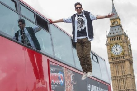 magician standing on nothing beside a bus