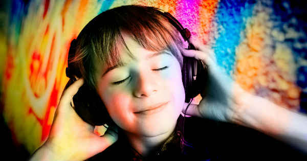 boy smiling while listening to a headset