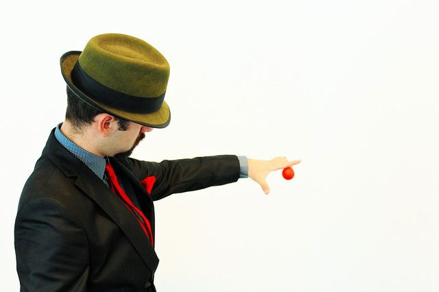 Majician holding a red small ball