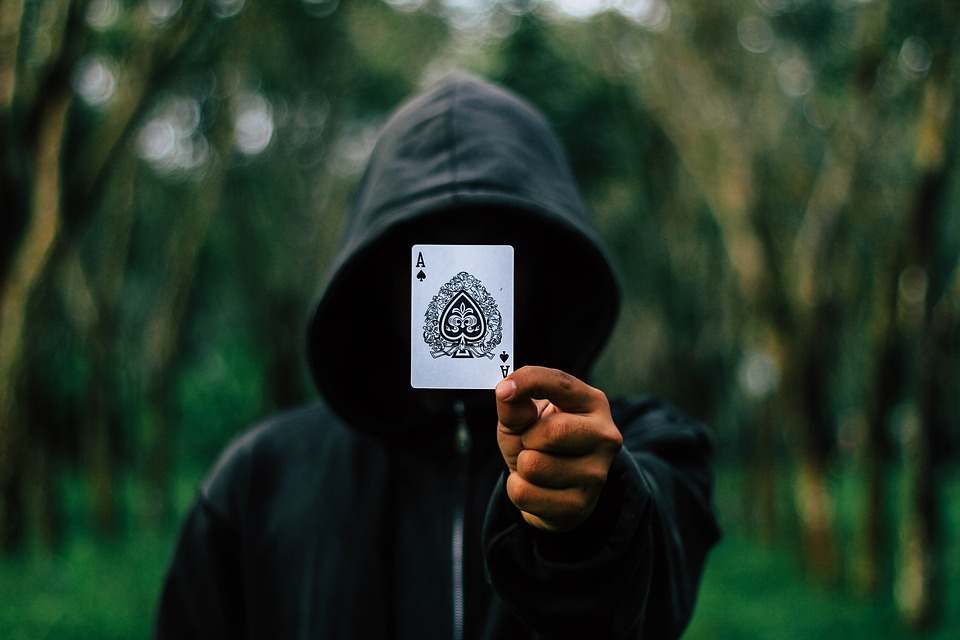 man in black hoodie holding ace card