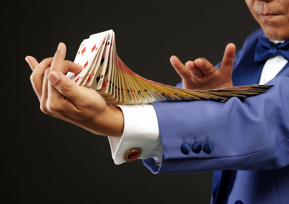 magician doing tricks with cards on his arm