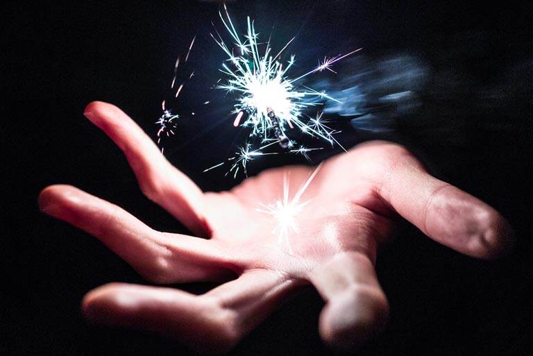 Man with sparkles above his hand