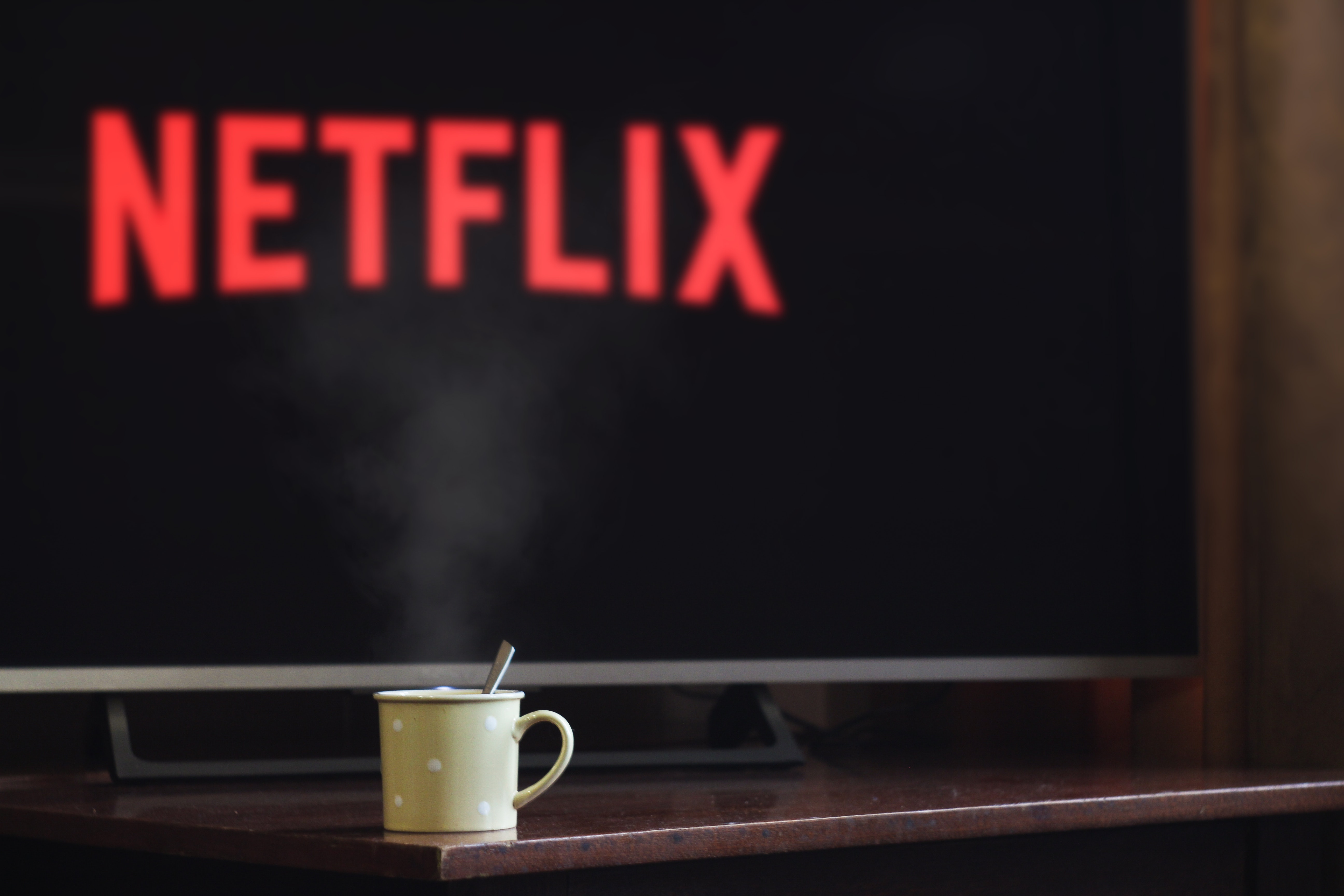 In front of a tv with netflix flashed on the screen is a cup of coffee