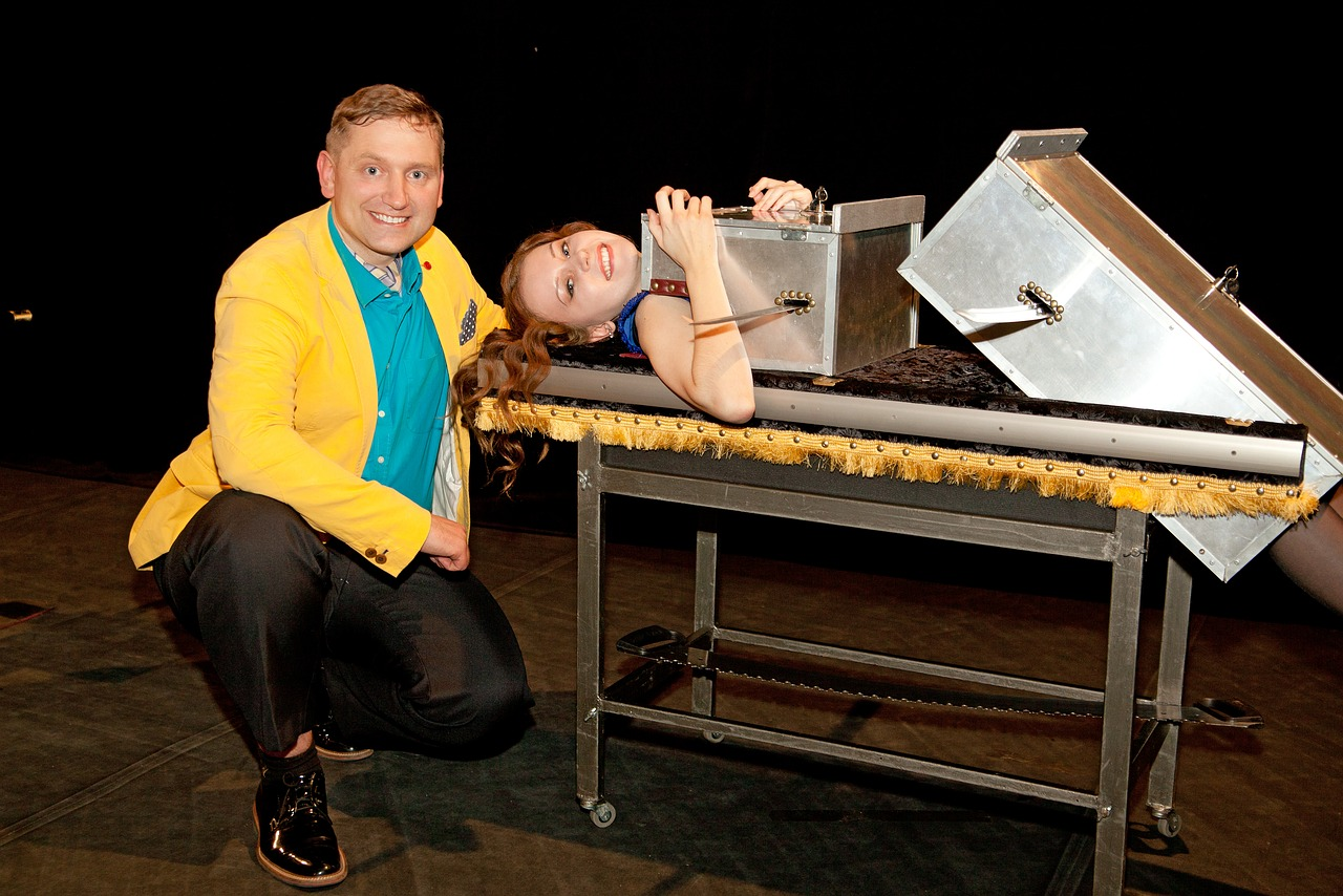 Magician performing a box illusion to a woman