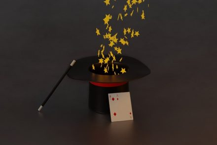 magician's hat, wand, and card with stars floating from the hat on gray background for magician books article